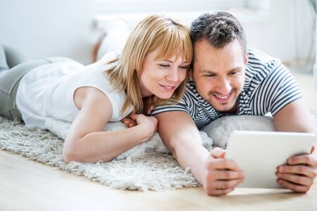 parejas de jovenes: Couple with tablet lying on floor and surfing the net