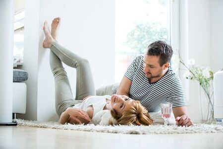 put together: Young couple lying in living room on carpet