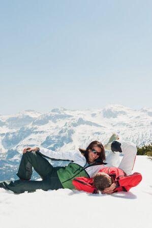 mid adult couple: Austria, Salzburgo Pa�s, Mediados pareja adulta tumbado en la nieve en invierno Foto de archivo