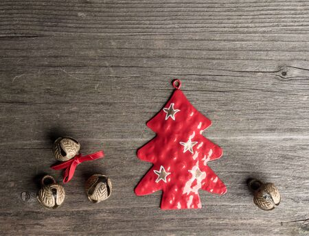 christmastime: Christmas decoration of metal, christmas tree, bells on wood