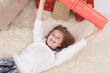 holding aloft: Boy lying on back and holding Christmas gift, smiling, portrait