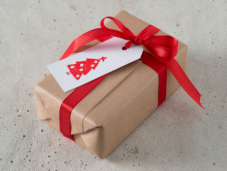 christmastime: Christmas present with gift tag, printed, red ribbon Stock Photo