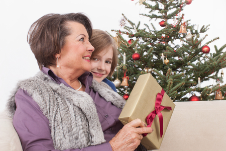 generation gap: Grandmother and grandson smiling, Christmas tree in background Stock Photo