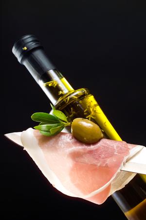 oil bottle: Knife with raw parma ham, green olive, olive oil bottle, black background