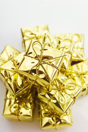 gift spending: Many small christmas presents in gold foil Stock Photo