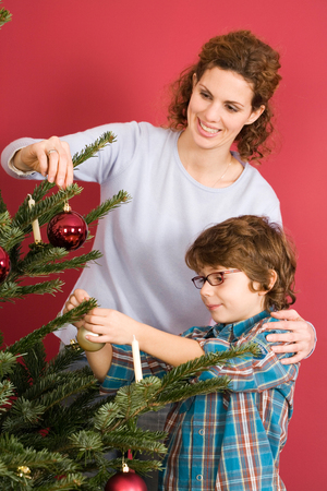 decorating christmas tree: Mother and son decorating Christmas tree Stock Photo