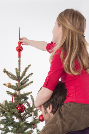 topper: Girl sitting on mans shoulders and positioning tree topper