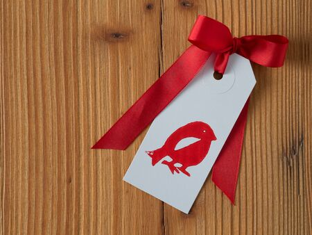 gift tag: Christmas, gift tag, printed, red ribbon, background wood Stock Photo