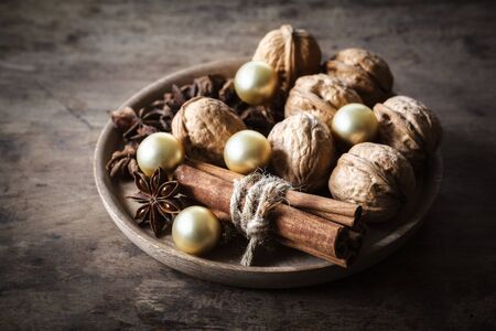 christmas scent: Christmas decorated bowl with walnuts and cinnamon sticks on dark wood