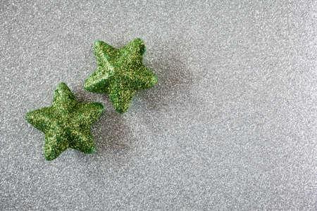 still lifes: Green stars on silver shiny underground Stock Photo