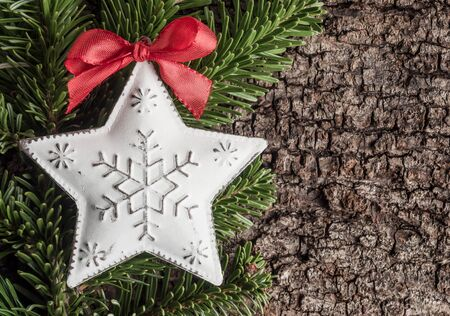christmastime: Christmas decoration on bark, evergreens, star of metal Stock Photo