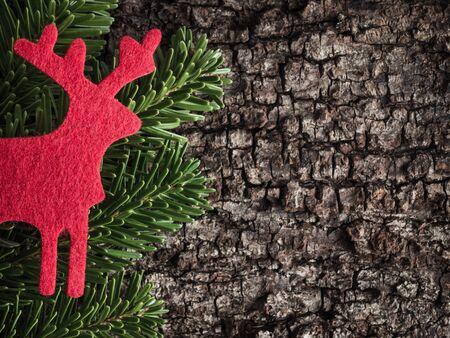 evergreens: Christmas decoration on bark, evergreens, reindeer of felt Stock Photo