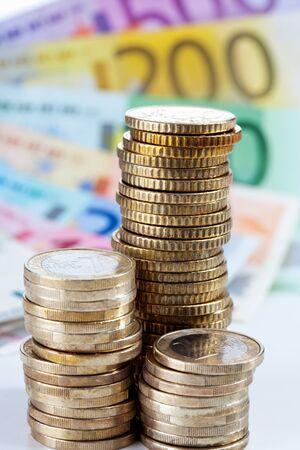 billets euros: Pile de pièces de monnaie en euros sur des billets en euros Banque d'images