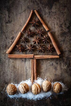 christmas scent: Christmas tree of cinnamon sticks, star anise and walnuts on dark wood