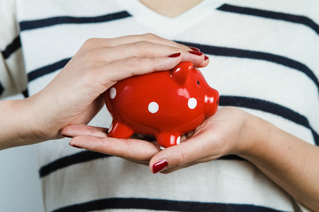 oldage: Woman holding red piggy bank
