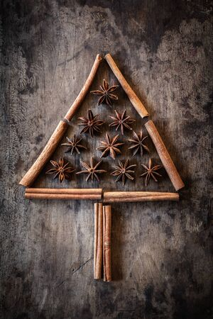 decorating christmas tree: Christmas tree of cinnamon sticks and star anise on dark wood