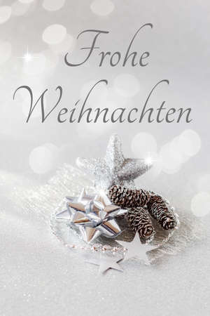 christmastime: Christmas arrangement with decorations, silver, German wishes, Merry Christmas