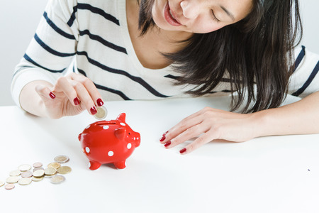 save: Woman saving money with red piggy bank Stock Photo