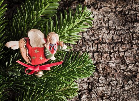 christmastime: Christmas decoration on bark, evergreens, angel