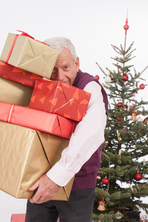 hair wrapped up: Senior man holding stack Christmas gifts, smiling, portrait