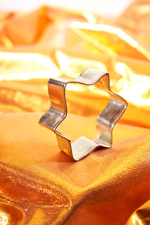 cookie cutter: Cookie cutter, star-shaped, on golden cloth