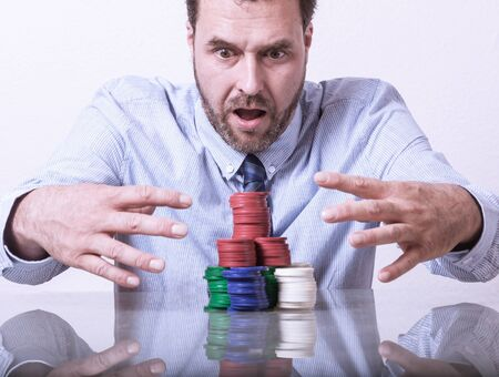 gamblers: Mature man with poker chips on glass table, looking greedy Stock Photo