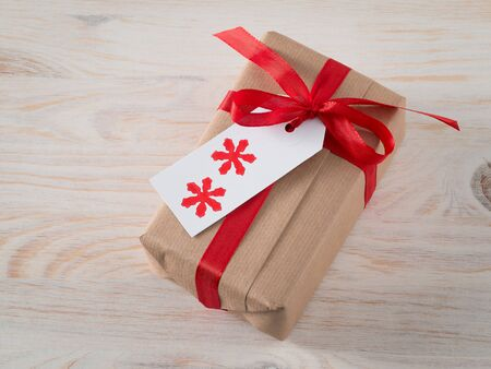 tag: Christmas present with gift tag, printed, red ribbon Stock Photo