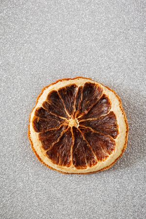 christmastime: Dried orange slice on silver shiny underground Stock Photo