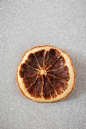 Rodaja de naranja seca en subterráneo de plata brillante