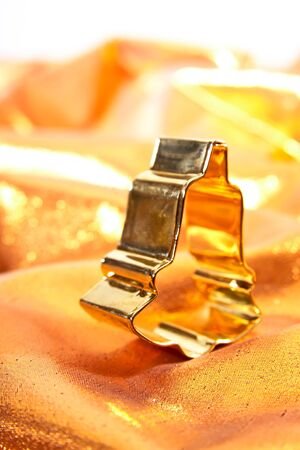 cookie cutter: Cookie cutter, bell-shaped, on golden cloth