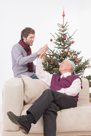 legs crossed at knee: Senior man and adult man high fiving, smiling