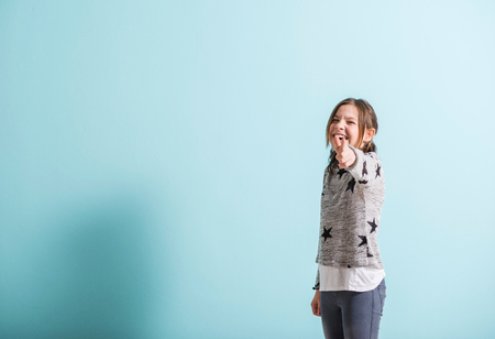 children hands: Laughing young girl pointing with finger Stock Photo