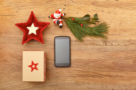 wood figurine: Christmas present, mobile phone, fir twig and Santa Claus figurine on wood