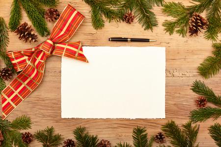 ballpen: Blank card, ballpen, fir twigs and ribbon, on wood