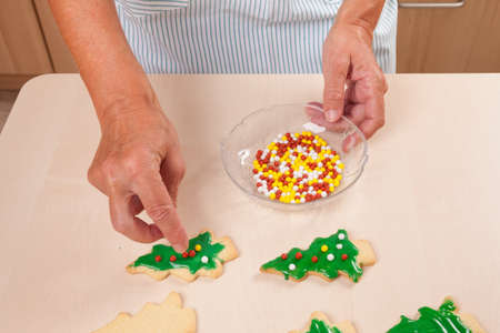 hundreds and thousands: Woman laying sugar pearls on Christmas biscuits