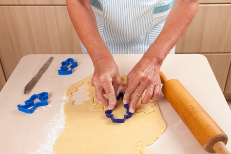 pastry cutters: Woman cutting out dough, rolling pin, dough, flour and pastry cutters Stock Photo