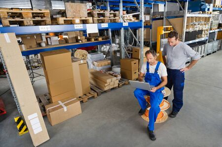 warehouseman: Germany,Bavaria,Munich,Manual workers using laptop in warehouse