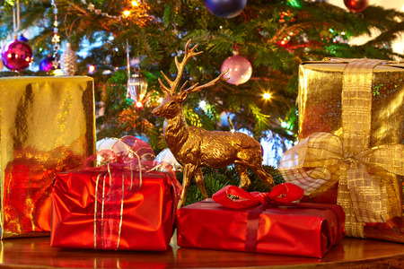 christmas tree presents: Christmas presents and deer figurine in front of Christmas tree