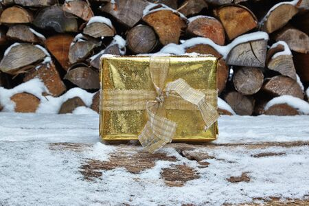 woodpile: Golden Christmas present in front of woodpile
