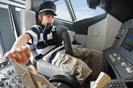 Germany,Bavaria,Munich,boy wearing captains hat and playing in airplane cockpit