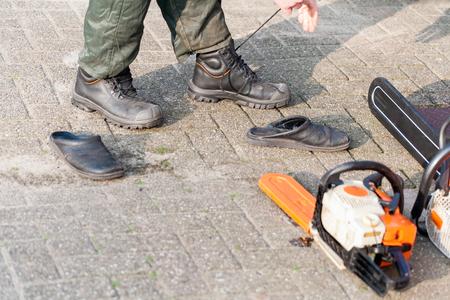 logging industry: Netherlands, Lumberjack changing shoes Stock Photo