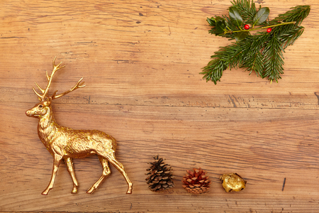 deer: Christmas decoration, deer figure, cones and fir branch on wood