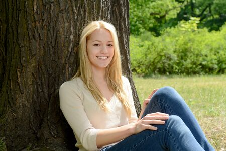 young tree: Young woman leaning on tree in park
