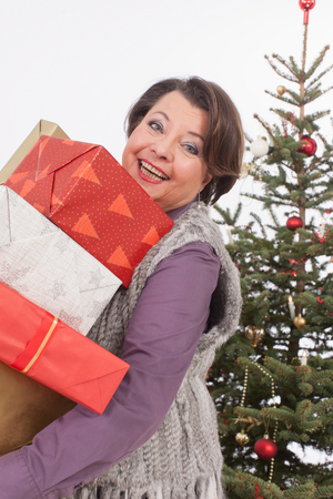 only senior adults: Senior woman holding Christmas gifts, smiling, portrait Stock Photo