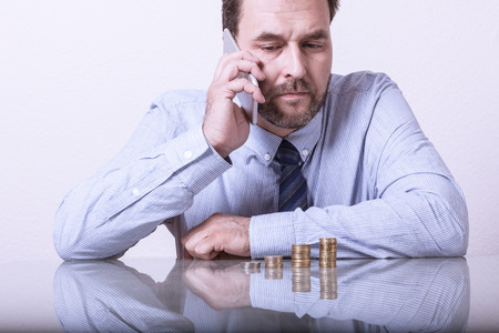 smart investing: Mature man at desk with stacked euro coins using smart phone
