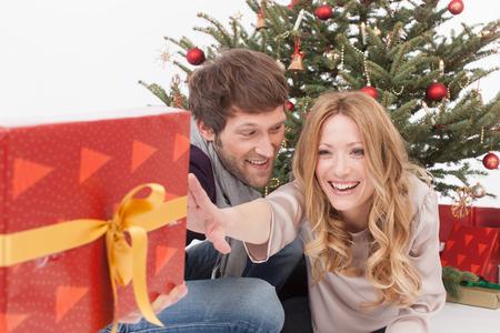 holding aloft: Woman reaching Christmas gift to man, smiling