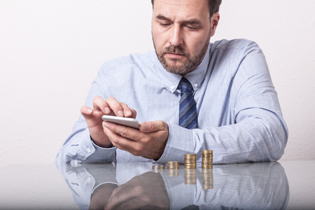 money savings: Mature man at desk with stacked euro coins using smart phone