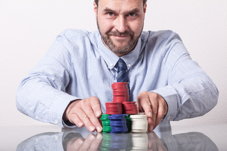 bet: Mature man with poker chips on glass table, placing his bet Stock Photo