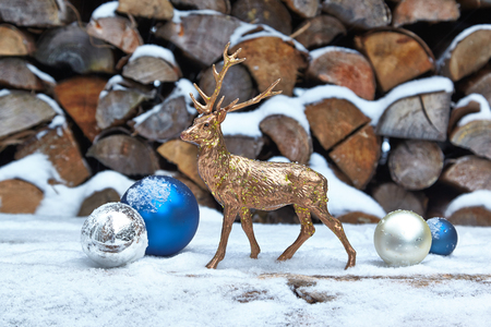 deer: Deer figurine and baubles in snow, woodpile