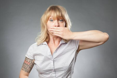 obscuring: Young woman portrait on grey background, covering her mouth Stock Photo
